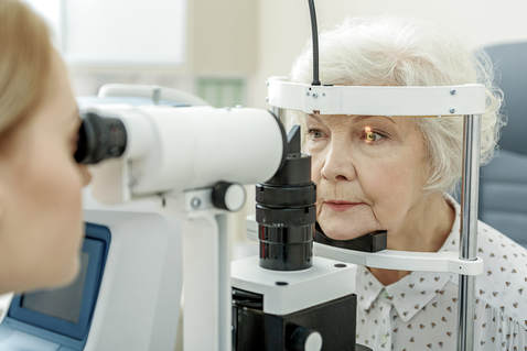 doctor doing dry eye evaluation on older lady